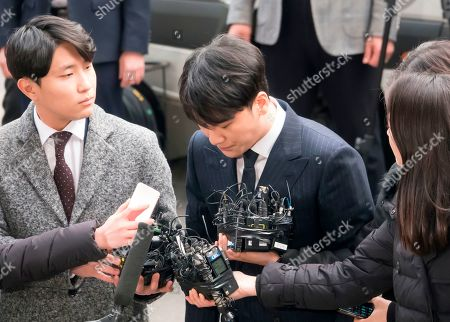 Lee Seung-hyun (C), a member of K-pop boy band BIGBANG, bows as he arrives at the Seoul Metropolitan Police Agency for police questioning over sex-for-favors allegations