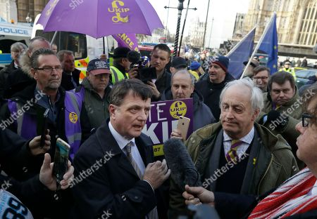 UKIP leader Gerard Batten, center left, and politician Neil Hamilton, right, join an anti-EU protest outside the Houses of Parliament in London,. British lawmakers faced another tumultuous day Thursday, as Parliament prepared to vote on whether to request a delay to the country's scheduled departure from the European Union and Prime Minister Theresa May struggled to shore up her shattered authority