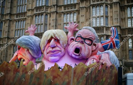 Effigies of British politicians from left, Prime Minister Theresa May, Boris Johnson and Michael Gove are driven on a truck by anti-Brexit, remain in the European Union supporters outside the Houses of Parliament in London, . British lawmakers faced another tumultuous day Thursday, as Parliament prepared to vote on whether to request a delay to the country's scheduled departure from the European Union and Prime Minister Theresa May struggled to shore up her shattered authority