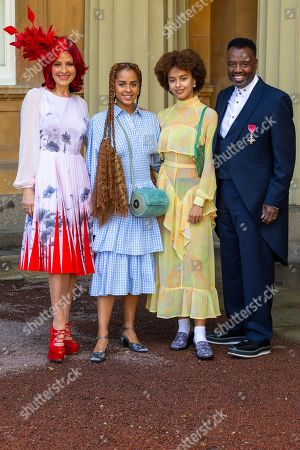 Musician David Grant proudly displays his OBE for services to music, accompanied by his wife Carrie, left and actress daughters Olive Gray, 24 (Save Me, Sex Education) and Talia, 17 (Hollyoaks) following an investiture ceremony at Buckingham Palace