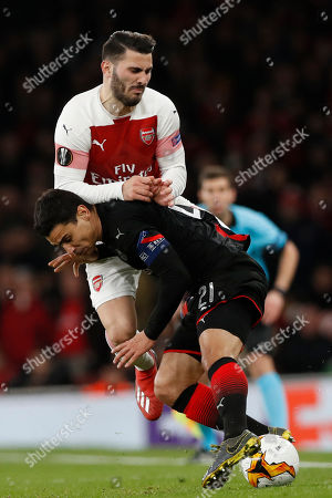 Arsenal's Sead Kolasinac, top, fights for the ball with Rennes' Benjamin Andre during the Europa League round of 16, 2nd leg, soccer match between Arsenal and Rennes at the Emirates stadium in London