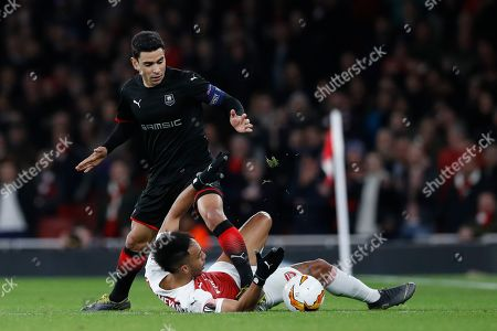 Arsenal's Pierre-Emerick Aubameyang, bottom, fights for the ball with Rennes' Benjamin Andre during the Europa League round of 16, 2nd leg, soccer match between Arsenal and Rennes at the Emirates stadium in London