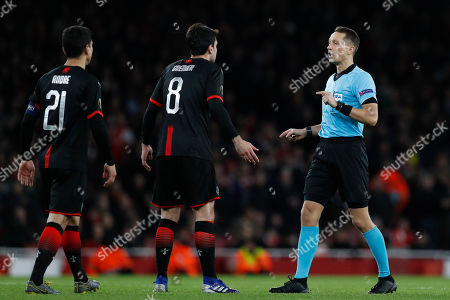 Latvian referee Andris Treimanis, right, speaks with Rennes' Clement Grenier, center, and Rennes' Benjamin Andre during the Europa League round of 16, 2nd leg, soccer match between Arsenal and Rennes at the Emirates stadium in London