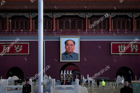 A Chinese honor guard marches out beneath the large portrait of Chinese leader Mao Zedong to perform the daily flag raising ceremony at Tiananmen Square on the eve of the closing session of China's National People's Congress (NPC) in Beijing