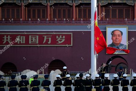 A Chinese honor guard opens the Chinese national flag in front of the portrait of Chinese leader Mao Zedong during the daily flag raising ceremony at Tiananmen Square on the eve of the closing session of China's National People's Congress (NPC) in Beijing