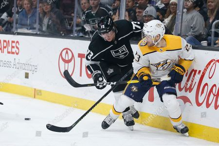 Los Angeles Kings forward Tyler Toffoli (73) and Nashville Predators forward Rocco Grimaldi (23) vie for the puck during an NHL hockey game between Los Angeles Kings and Nashville Predators, in Los Angeles. The Predators won 3-1