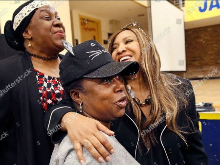 Stock Photo of Cheryl Smart, Stephanie Chauncey, Lynne Patton. Queensbidge Houses residents Cheryl Smart, left, and Resident Association Vice President Stephanie Chauncey, center, share a laugh as they pose for a photograph with HUD executive Lynne Patton following the conclusion of a town hall style meeting at the housing project's gymnasium in New York. Patton spent one month living in four New York City public housing projects to learn about residents' complaints, monitor oversight, and offer solutions to NYCHA's persistent and recurring problems