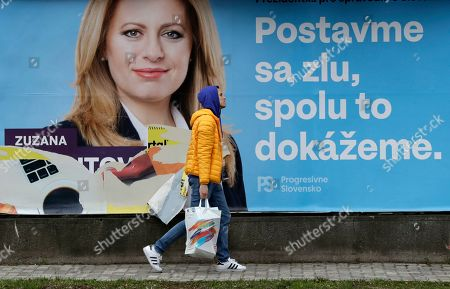 "A man walks past a campaign poster for Zuzana Caputova in Bratislava, Slovakia, . Caputova is one of the favorite candidates to succeed Slovakia's President Andrej Kiska in the upcoming election. Slovakia holds the presidential election on Saturday, March 16, 2019. The poster reads: ""Let's stand against evil, together we can make it"