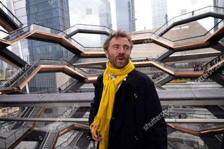 "British designer Thomas Heatherwick climbs the steps of ""Vessel"" on its opening day at Hudson Yards, in New York. Hudson Yards, a $25 billion urban complex on Manhattan's west side, is the city's most ambitious development since the rebuilding of the World Trade Center. When fully complete, the 28-acre site will include 16 towers of homes and offices, a shopping mall, hotel, school, the highest outdoor observation deck in the Western Hemisphere, a performing arts center and Vessel"