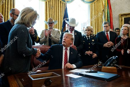 """Stock Photo of President Donald Trump shakes hands with Mary Ann Mendoza, an """"Angel Mom"""" who lost her son Brandon when he was killed by a drunk driver that was an undocumented immigrant, before signing the first veto of his presidency in the Oval Office of the White House, in Washington. Trump issued the first veto, overruling Congress to protect his emergency declaration for border wall funding"""