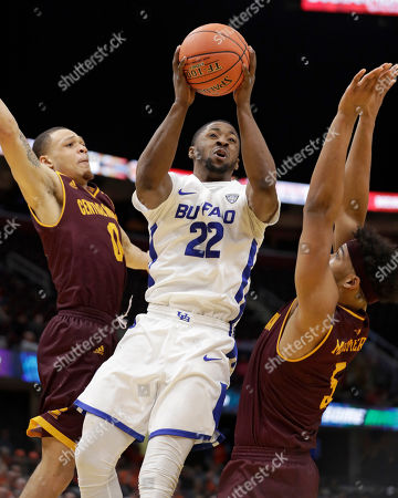 Dontay Caruthers, Larry Austin Jr., Robert Montgomery. Buffalo's Dontay Caruthers (22) drives to the basket between Central Michigan's Larry Austin Jr. (0) and Robert Montgomery (5) during the second half of an NCAA college basketball game in the semifinals of the Mid-American Conference men's tournament, in Cleveland. Buffalo won 85-81