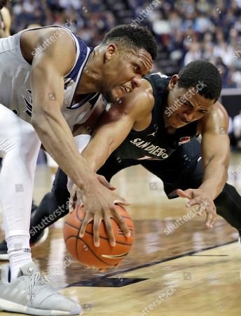 San Diego State's Matt Mitchell, right, and Nevada's Tre'Shawn Thurman reach for a loose ball during the first half of an NCAA college basketball game in the Mountain West Conference men's tournament, in Las Vegas