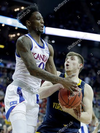Kansas' Marcus Garrett (0) tries to steal the ball from West Virginia's Logan Routt during the first half of an NCAA college basketball game in the Big 12 men's tournament, in Kansas City, Mo