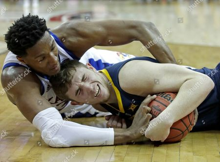 Kansas' David McCormack, left, tries to wrestle the ball away from West Virginia's Logan Routt during the second half of an NCAA college basketball game in the Big 12 men's tournament, in Kansas City, Mo. Kansas won 88-74