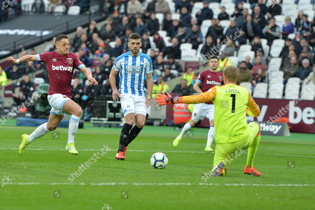 Jonas Lossl of Huddersfield Town closes down Javier Hernandez of West Ham United during West Ham United vs Huddersfield Town, Premier League Football at The London Stadium on 16th March 2019
