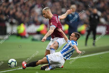 CAPTION CORRECTION: Chris Lowe of Huddersfield Town tackles Marko Arnautovic of West Ham United
