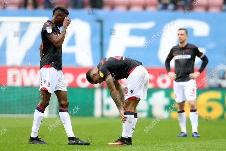 Sammy Ameobi, Josh Magennis and Andrew Taylor of Bolton Wanderers show a look of dejection after Wigan Athletic score the fourth goal to make the score 4-2