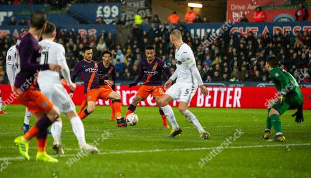 David Silva of Manchester City has a shot at goal which is saved by Kristoffer Nordfeldt goalkeeper of Swansea City