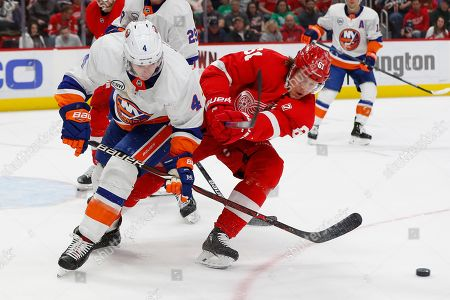 New York Islanders defenseman Thomas Hickey (4) and Detroit Red Wings center Jacob de la Rose (61) battle for the puck in the second period of an NHL hockey game, in Detroit