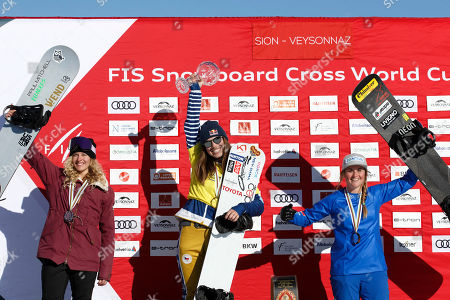 Czech Republic's Eva Samkova lifts the crystal globe of the overall Ladies' Snowboard Cross World Cup, between USA Lindsey Jacobellis, left, placed second, and Italy's Michela Moiolo, right, placed third, on the podium at the FIS Ski Cross World Cup Finals, at the FIS Snowboard Cross World Cup Finals, in Veysonnaz, Switzerland, Saturday, March 16, 2019.