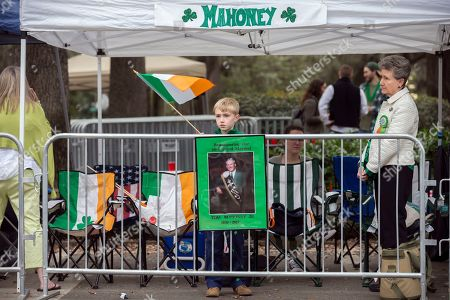 Matthew Taylor stands near a photo that memorializes his grandfather Tom Mahoney Jr., before the start of the Savannah St. Patrick's Day parade, in Savannah, Ga