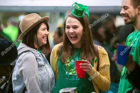 Stock Photo of Ashleigh Burns, center, laughs with her friend Emily Doyle, left, before the start of the 195-year-old Savannah St. Patrick's Day parade, in Savannah, Ga