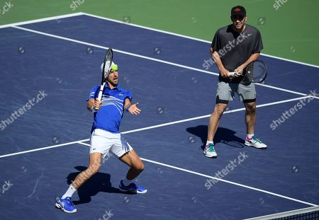Stock Image of Novak Djokovic, left, returns a shot alongside former professional tennis player Pete Sampras, as they play doubles against former players Tommy Haas and John McEnroe at the BNP Paribas Open tennis tournament, in Indian Wells, Calif