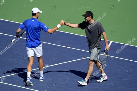 Novak Djokovic, left, reacts with former professional tennis player Pete Sampras, as they play a doubles exhibition match against former players Tommy Haas and John McEnroe at the BNP Paribas Open tennis tournament, in Indian Wells, Calif