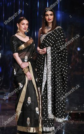 Bollywood actresses Aditi Rao Hydari, left, and Diana Penty display creations of top Indian designers celebrating Sari, an Indian women wear, during the Grand finale of the Lotus make up India Fashion Week in New Delhi, India