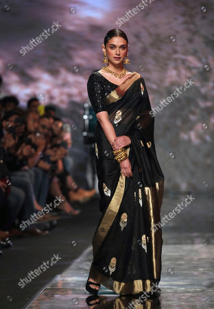 Bollywood actress Aditi Rao Hydari displays a creation of one of the top Indian designers celebrating Sari, an Indian women wear, during the Grand finale of the Lotus make up India Fashion Week in New Delhi, India
