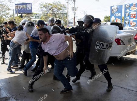 Members of the National Police try to stop the photojournalist Luis Sequeira, of the AFP agency, during a demonstration against the government of Daniel Ortega in Managua, Nicaragua, 16 March 2019. The Nicaraguan police allegedly violently withdrew on the same day a group of journalists who were covering an anti-government demonstration, in the context of the serious socio-political crisis affecting the country.