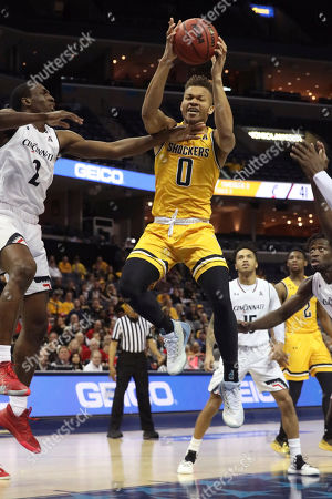 Wichita State's Dexter Daniels goes for the goal as Cincinnati player Keith Williams defends in the first half of an NCAA college basketball game at the American Athletic Conference tournament, in Memphis, Tenn