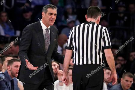 Villanova head coach Jay Wright, left, talks to referee Pat Driscoll during the first half of an NCAA college basketball game against Seton Hall in the championship of the Big East Conference tournament, in New York. Villanova won 74-72