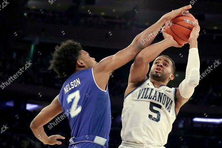 Villanova guard Phil Booth (5) goes up for a shot against Seton Hall guard Anthony Nelson (2) during the first half of an NCAA college basketball game in the championship of the Big East Conference tournament, in New York