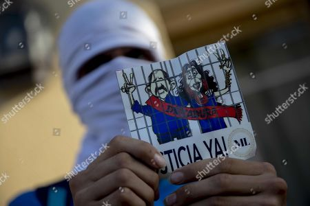 A young man holds a picture with drawings of President Daniel Ortega and his wife Rosario Murillo during a anti-government protest in Managua, Nicaragua, 16 March 2019. Nicaragua's police arrested at least 31 people including journalists, opposition leaders, a Sandinista former guerrilla and a former Minister of Education, prior to an anti-government demonstration. The arrests were made in the first kilometers of the Carretera a Masaya, the point where there would be a march to demand from President Daniel Ortega the 'unconditional and absolute' release of 'political prisoners'.
