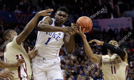Duke's Zion Williamson, center, loses the ball as he is trapped by Florida State's David Nichols, right, and Raiquan Gray, left, during the first half of the NCAA college basketball championship game of the Atlantic Coast Conference tournament in Charlotte, N.C