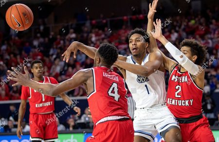 Old Dominion guard Jason Wade (1) passes around the defense of Western Kentucky guards Josh Anderson (4) and Jared Savage (2) during the second half of an NCAA college basketball game for the Conference USA men's tournament championship, in Frisco, Texas. Old Dominion won 62-56