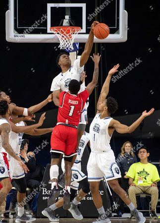 Old Dominion forward Kalu Ezikpe blocks a shot by Western Kentucky guard Lamonte Bearden (1) as Old Dominion's Jason Wade (1) also defends during the second half of an NCAA college basketball game for the Conference USA men's tournament championship, in Frisco, Texas. Old Dominion won 62-56