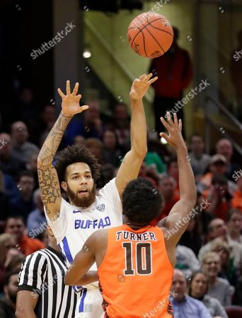 Buffalo's Jeremy Harris, back, passes against Bowling Green's Justin Turner during the first half of an NCAA college basketball championship game of the Mid-American Conference men's tournament, in Cleveland