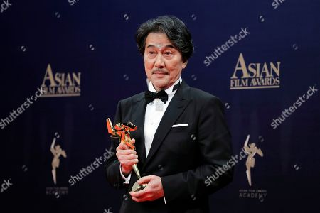 Japanese actor Koji Yakusho poses after winning the Excellence in Asian Cinema Award of the Asian Film Awards in Hong Kong