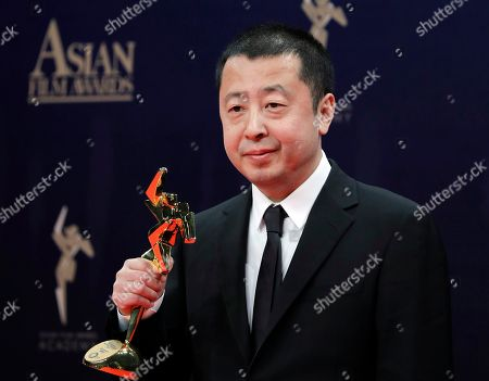 Chinese director Jia Zhangke poses after winning the Best Screenplay Award of the Asian Film Awards in Hong Kong