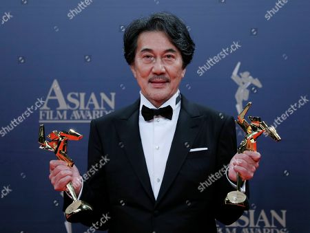 Japanese actor Koji Yakusho poses after winning the Best Actor and Excellence in Asian Cinema Award of the Asian Film Awards in Hong Kong