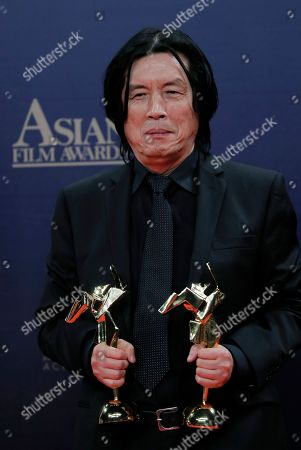 Stock Image of South Korea director Lee Chang-dong poses after winning the Best Director Award of the Asian Film Awards in Hong Kong