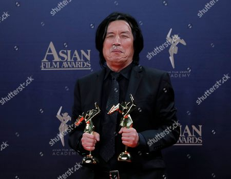 South Korea director Lee Chang-dong poses after winning the Best Director Award of the Asian Film Awards in Hong Kong