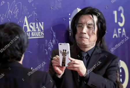 South Korea director Lee Chang-dong takes a photo on the red carpet of the Asian Film Awards in Hong Kong