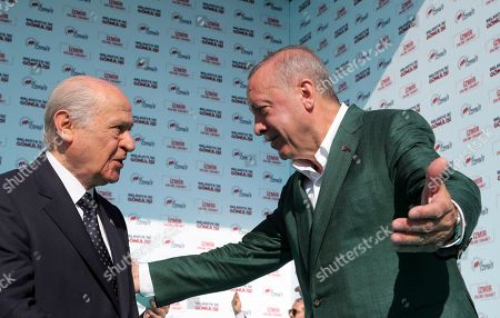 Turkey's President Recep Tayyip Erdogan, right, and Devlet Bahceli, the leader of opposition Nationalist Movement Party, MHP, speak as they salute the supporters of MHP and ruling Justice and Development Party, AKP, during a joint rally in Aegean city of Izmir, Turkey, . Erdogan's AKP and MHP made an alliance for the countrywide local elections scheduled for March 31, 2019 with 57 million registered voters