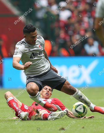 Toluca's Pablo Barrientos (down) vies for the ball with Atlas' Anderson Santamaria during their Mexican tournament soccer match between Toluca and Atlas at Nemesio Diez stadium in Toluca, Mexico, 17 March 2019.