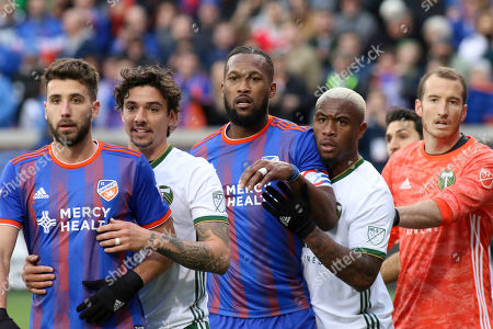 FC Cincinnati players Mathieu Deplagne (left) and Kendall Waston (center) wait for a corner kick along with Portland Timbers players Zarek Valentin (second left), Claude Dielna (second right), and Jeff Attinella (far right) during an MLS soccer game between FC Cincinnati and Portland at Nippert Stadium in Cincinnati, Ohio