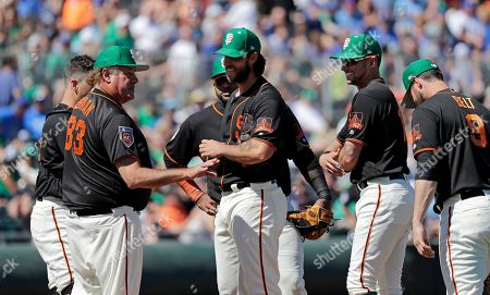 Stock Photo of Chris Berman, Madison Bumgarner. Sportscaster Chris Berman (83) talks with San Francisco Giants starting pitcher Madison Bumgarner, center, and infielders in his role as honorary manager for the day in the team's spring training baseball game against the Kansas City Royals, in Scottsdale, Ariz