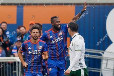 FC Cincinnati defender Kendall Waston, center, celebrates after scoring in the first half of an MLS soccer match against the Portland Timbers, in Cincinnati